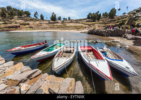 Colourful traditional wooden rowing boats moored in harbour in Taquile Island, Lake Titicaca, Altiplano, Puno region, - Stock Photo