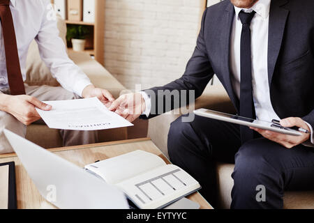 Businessman giving document to his colleague at meeting - Stock Photo