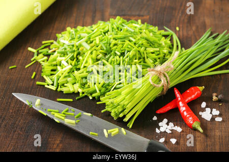 Fresh chives on chopping board - Stock Photo
