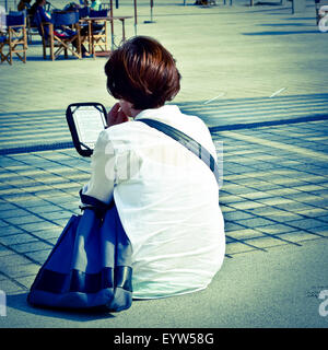 Woman sitting on a bench back. She holds an ebook device and reads. - Stock Photo