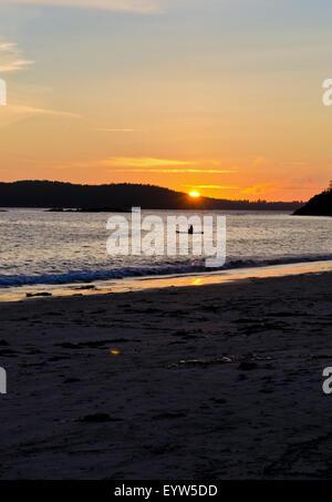 Beautiful sunset at Mackenzie Beach in Tofino.  Person sitting on paddle board watching the sunset. - Stock Photo