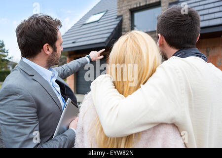 View of a Real estate agent shows details to customers - Stock Photo