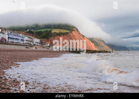Sea front at Sidmouth, clouds rolling across cliff tops. - Stock Photo