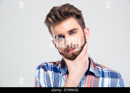 Portrait of a handsome man touching his chin isolated on a white background. Looking at camera - Stock Photo
