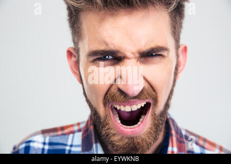 Portrait of a young man screaming isolated on a white background. Looking at camera - Stock Photo