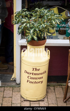Old milk churn used outside a shop in Dartmouth to hold a plant and show the shop's identity - Stock Photo