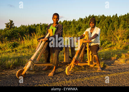 Local boys on their self-made bicycles, Malawi, Africa - Stock Photo