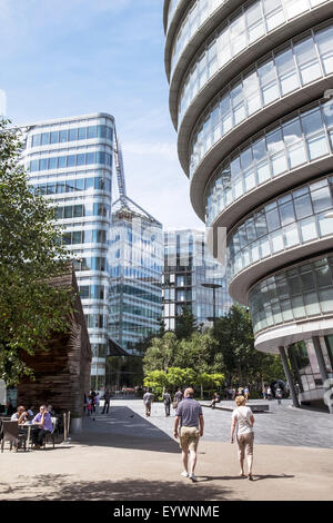 Tourists strolling past London City Hall on the South Bank in London. - Stock Photo