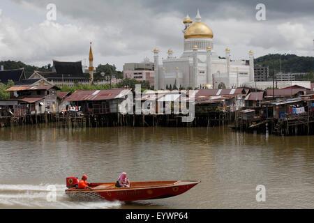 Boats past water village with Omar Ali Saifuddien mosque in Bandar Seri Begawan, Brunei, Southeast Asia, Asia - Stock Photo