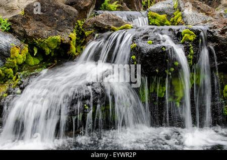 Small stream cascading over rocks in mountains of Kilauea, Kauai, Hawaii, United States of America, Pacific - Stock Photo