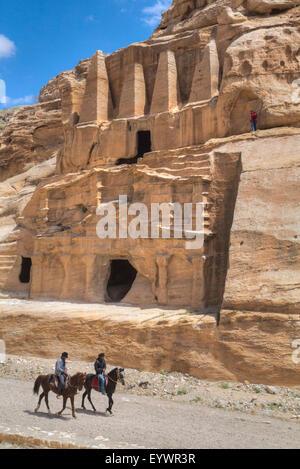 Local men on horses, Obelisk Tomb, upper structure, and Bab-as Siq Triclinium below, Petra, UNESCO, Jordan, Middle - Stock Photo