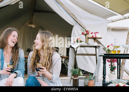 Two smiling women sitting outside a tent in a desert, enjoying a glass of wine. - Stock Photo