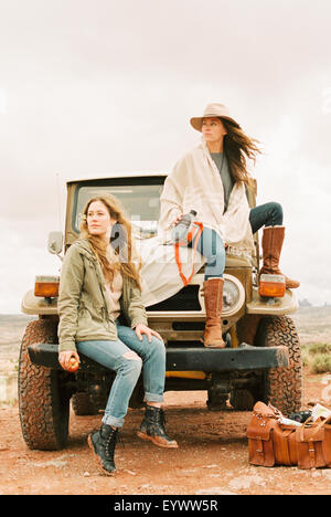 Two women sitting on the front of a jeep, on a road trip. - Stock Photo