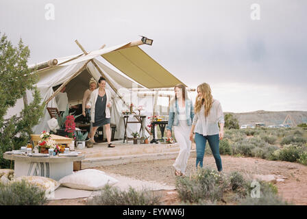 Group of friends enjoying an outdoor meal in a desert, a tent in the background. - Stock Photo
