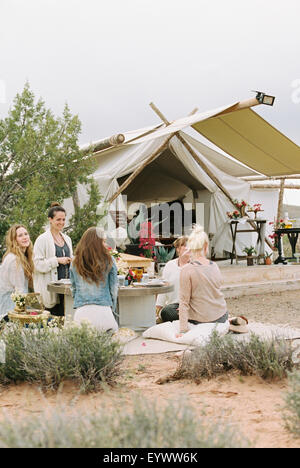 Group of women friends sitting on the ground round a table in a desert, a tent in the background. - Stock Photo