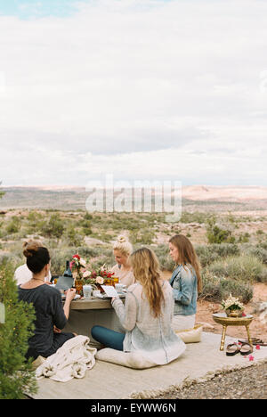 A group of women, friends sitting on the ground round a table in the open desert. - Stock Photo