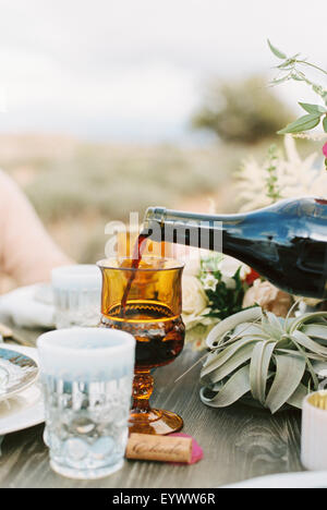 An outdoor meal in a desert, red wine being poured into a glass. - Stock Photo