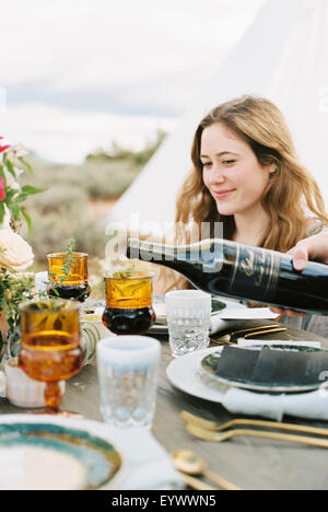 women gathered for meal, one pouring red wine from a bottle. Stock Photo