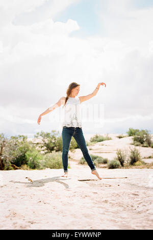 Barefoot woman wearing jeans her arms raised. - Stock Photo