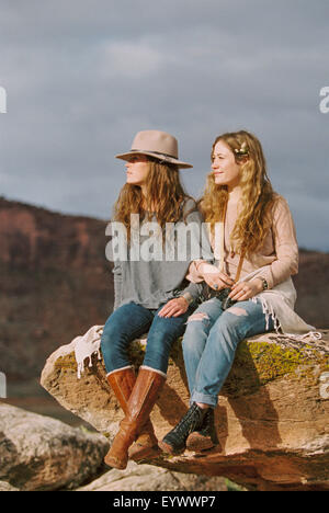 Two women wearing leather boots on rock in desert - Stock Photo