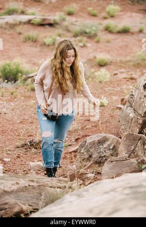 Woman walking past rocks in a desert. - Stock Photo