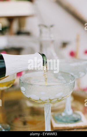 champagne being poured from bottle into a glass. - Stock Photo