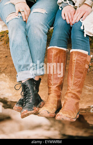 two women wearing leather boots sitting on a rock - Stock Photo