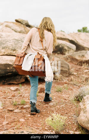 Woman walking in a desert carrying a leather bag. - Stock Photo