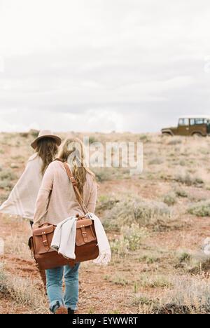 Two women walking towards 4x4 parked in a desert. - Stock Photo