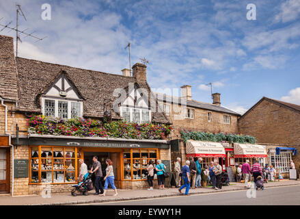 Tourists in the High Street at Bourton-on-the-Water, Gloucestershire, England. - Stock Photo