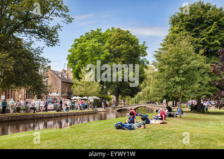 Tourists on a day out on a summer afternoon in the Cotswold village of Bourton-on-the-Water, Gloucestershire, England. - Stock Photo
