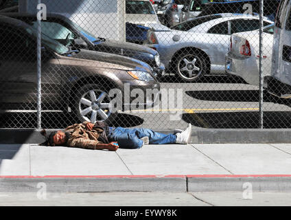 Los Angeles, CA, USA - September 23, 2011: Homeless man sleeps on the street near the fence in the center of Los - Stock Photo