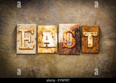 The word 'EAST' written in rusty metal letterpress type on an old aged leather background. - Stock Photo