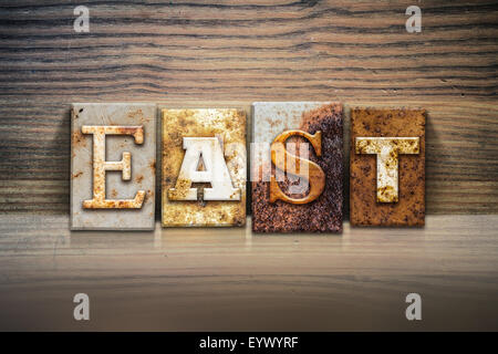 The word 'EAST' written in rusty metal letterpress type sitting on a wooden ledge background. - Stock Photo