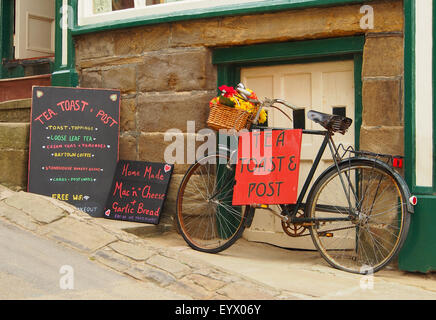 Bicycle sign advertising Tea, Toast and Post outside a cafe at Robin Hoods Bay Near Whitby on the Yorkshire coast - Stock Photo