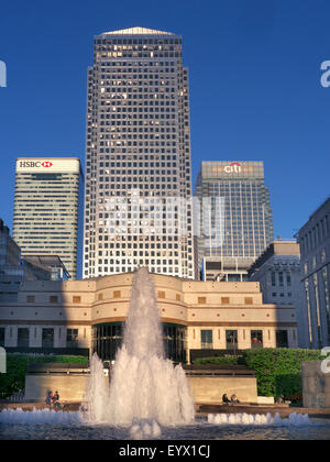 Late afternoon sun illuminates the towers in Cabot Square Canada One HSBC and CiTi Banks with fountains Canary Wharf - Stock Photo