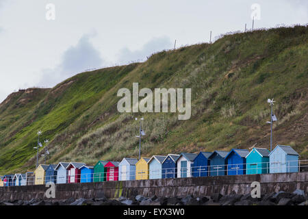Row of beach huts under a hill on the coast of Sheringham. - Stock Photo