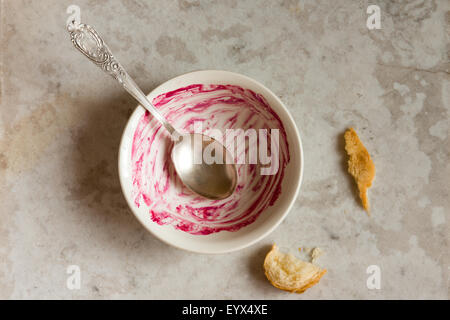 Dirty empty bowl and spoon (dish) after tasty breakfast over stone table - Stock Photo