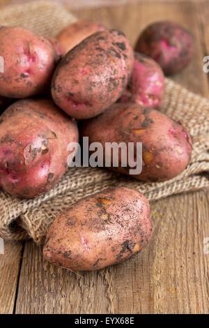 Raw organic potatoes over burlap and rustic wooden table - Stock Photo