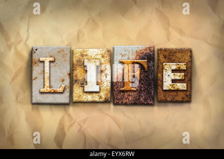 The word 'LIFE' written in rusty metal letterpress type on a crumbled aged paper background. - Stock Photo