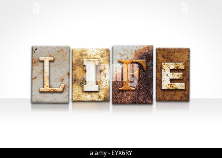 The word 'LIFE' written in rusty metal letterpress type isolated on a white background. - Stock Photo