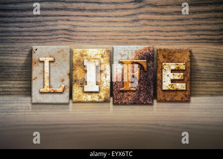 The word 'LIFE' written in rusty metal letterpress type sitting on a wooden ledge background. - Stock Photo