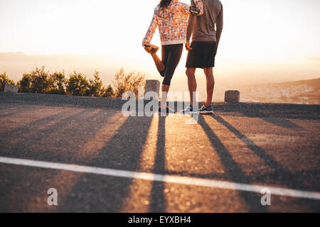Cropped shot of man and woman standing on hillside road in morning. Woman stretching her leg. Couple of joggers - Stock Photo