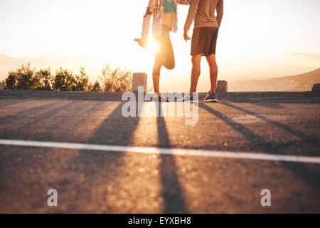 Cropped shot of fit young couple warming up before a run together at sunrise. Young man and woman exercising in - Stock Photo