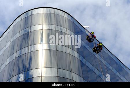 Suspended window cleaners cleaning windows high up on a modern glass fronted office block. - Stock Photo