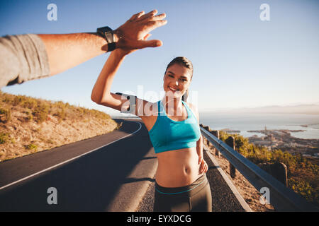Fit young woman giving high five to her boyfriend after a run. POV shot of couple high fiving on country road in - Stock Photo