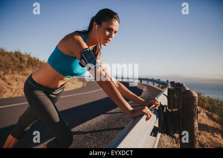 Young female athlete leaning on highway guardrail looking away. Woman runner outdoors on country road taking a break - Stock Photo