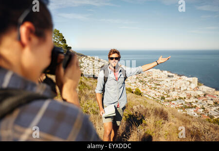 Outdoor shot of tourist couple enjoying nature and taking photo. Woman taking picture of boyfriend showing something - Stock Photo