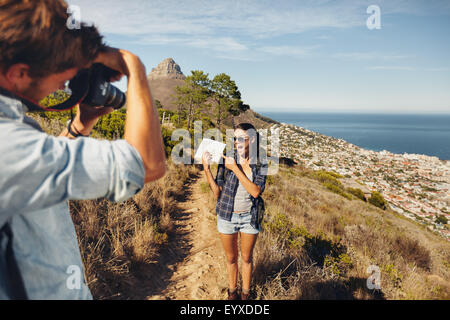 Excited young woman showing map and posing to his boyfriend taking her pictures with digital camera. Young couple - Stock Photo