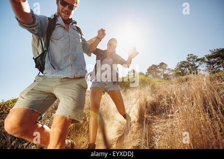 Portrait of happy young couple having fun on their hiking trip, sliding down the mountain trail. Caucasian hiker - Stock Photo